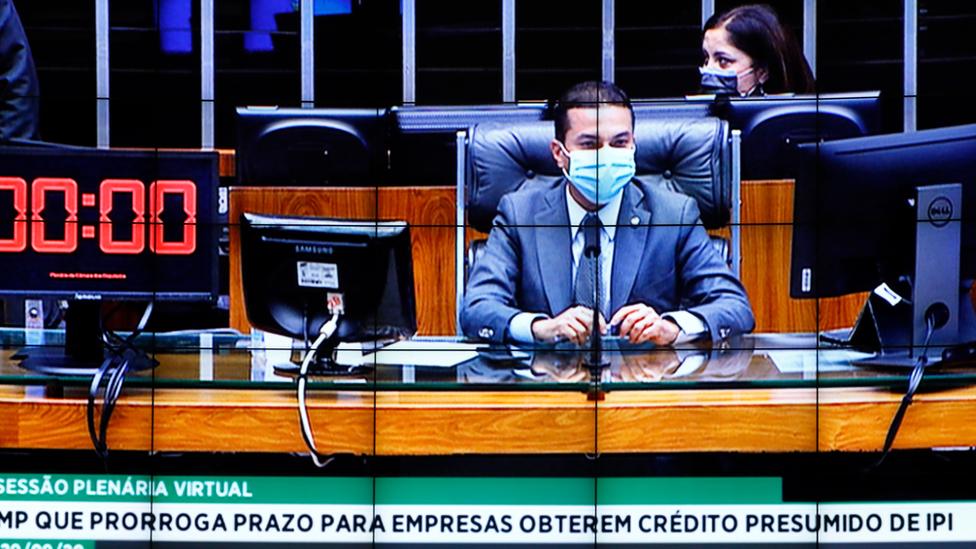 Foto do telão da câmara mostra deputado Marcos Pereira sentado à mesa, com máscara