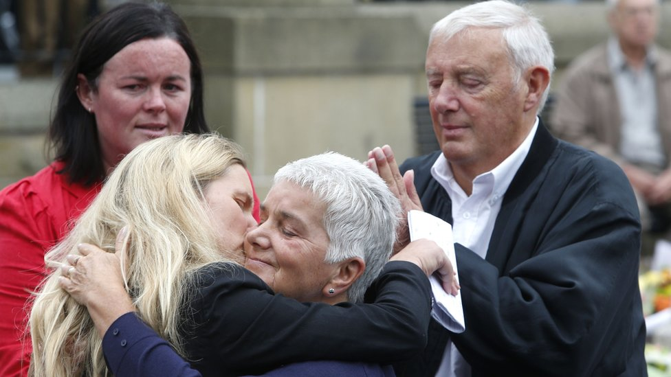 Jean Leadbeater, the mother of Labour MP Jo Cox, embraces her sister Kim Leadbeater while her father Gordon looks on, as they look at floral tributes left in Birstall, West Yorkshire
