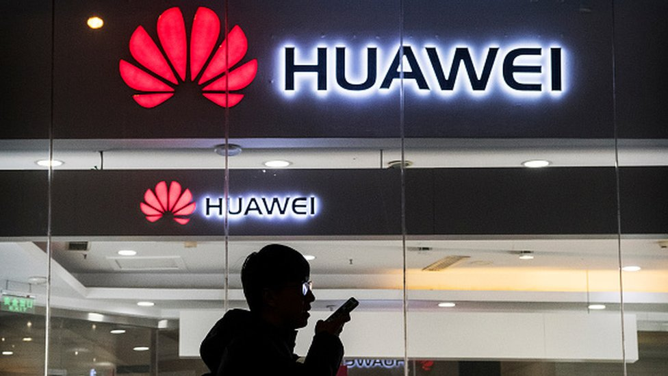 A pedestrian talks on the phone while walking past a Huawei store in Beijing