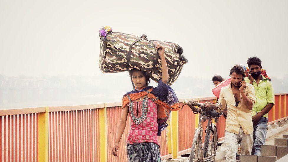 Mulher caminhando com sacola na cabeca