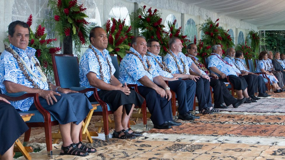 Leaders in matching shirts all sit in a line
