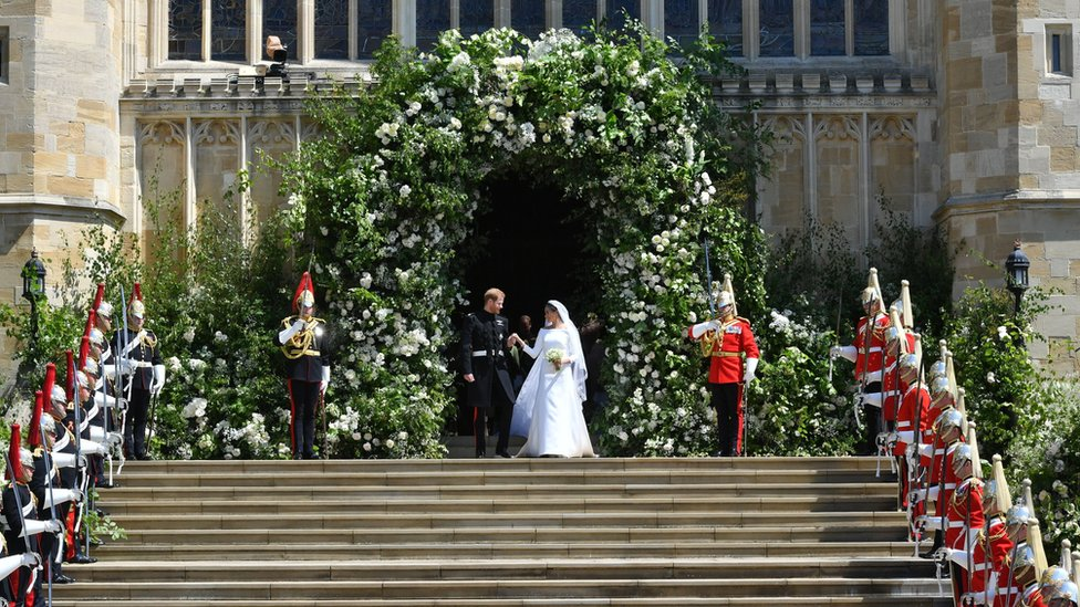 Prince Harry and Meghan Markle leave St George's Chapel though a gateway of flowers.