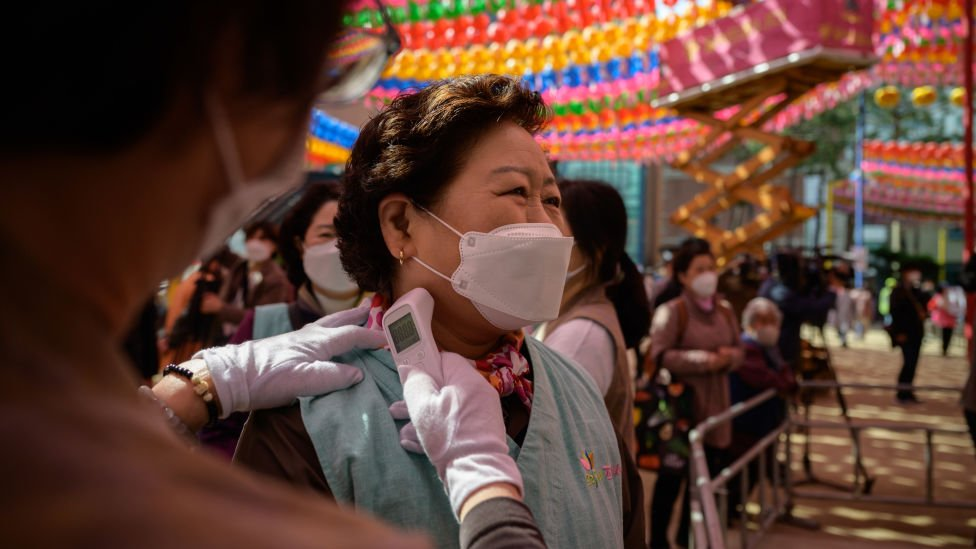 Worshippers wearing face masks have their temperature taken