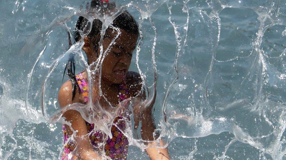 طفل يخترق زخات ماء منعشة في واشنطن.