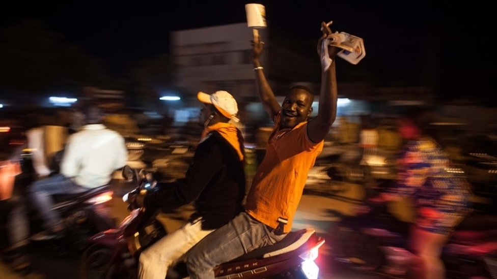 Supporters of presidential election candidate of Burkina Faso Roch Marc Christian Kabore, celebrate in the streets of the city, after preliminary results showed him to be the winner of recent elections in Ouagadougou, Burkina Faso, Tuesday, Dec. 1, 2015