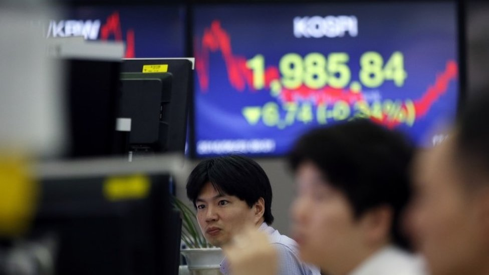 Currency traders watch computer monitors near the screen showing the Korea Composite Stock Price Index (KOSPI) at the foreign exchange dealing room in Seoul, South Korea, Thursday, June 23, 2016.