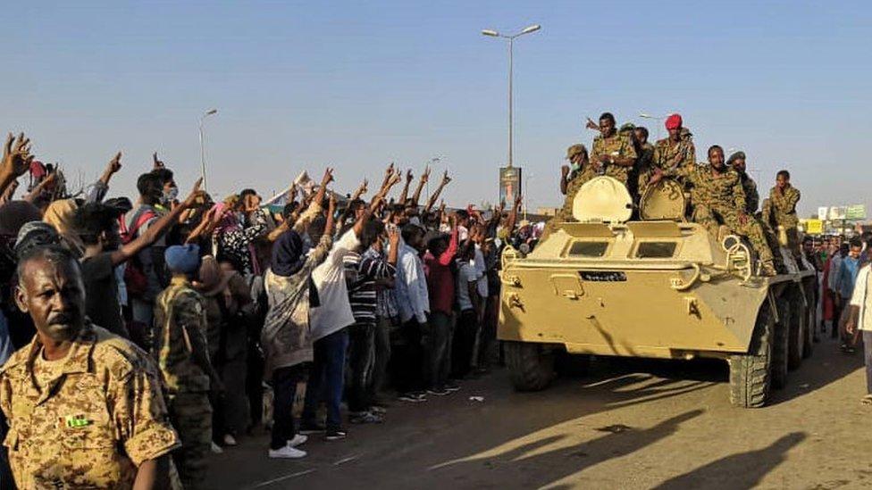 متظاهرون سودانيون يشيرون بعلامة النصر لمدرعة تابعة للجيش