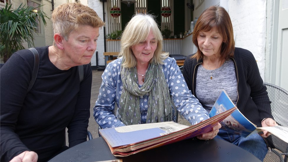 Chris, Leah and Gill look at their 1971 scrapbooks