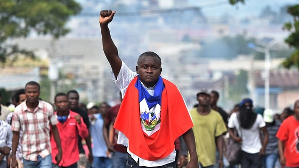 A man holds up his fist as demonstrators march through the streets of Port-au-Prince
