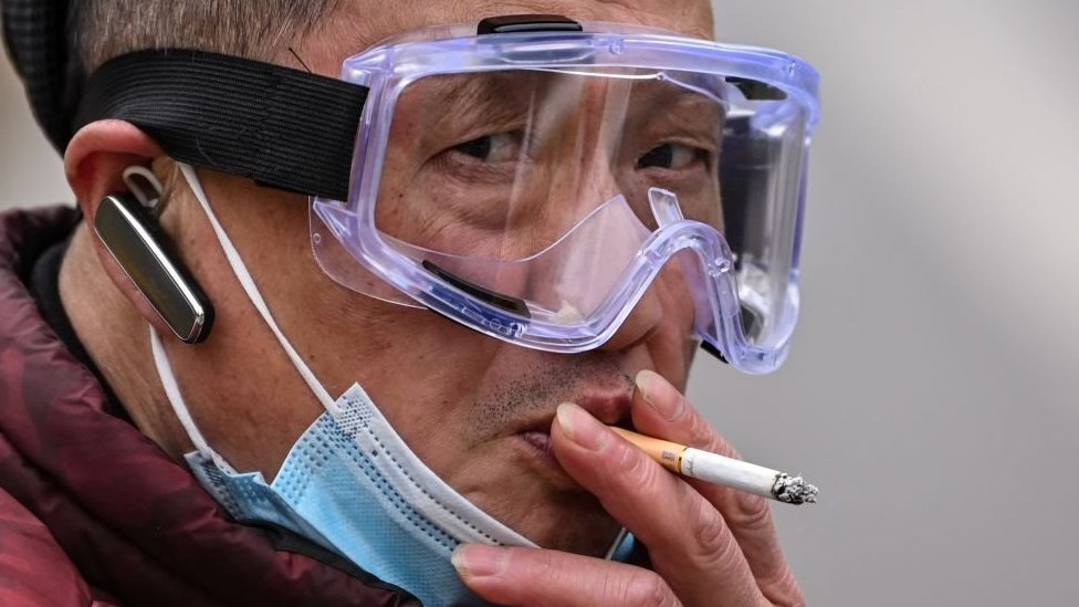 Man wearing face goggles smoking a cigarette