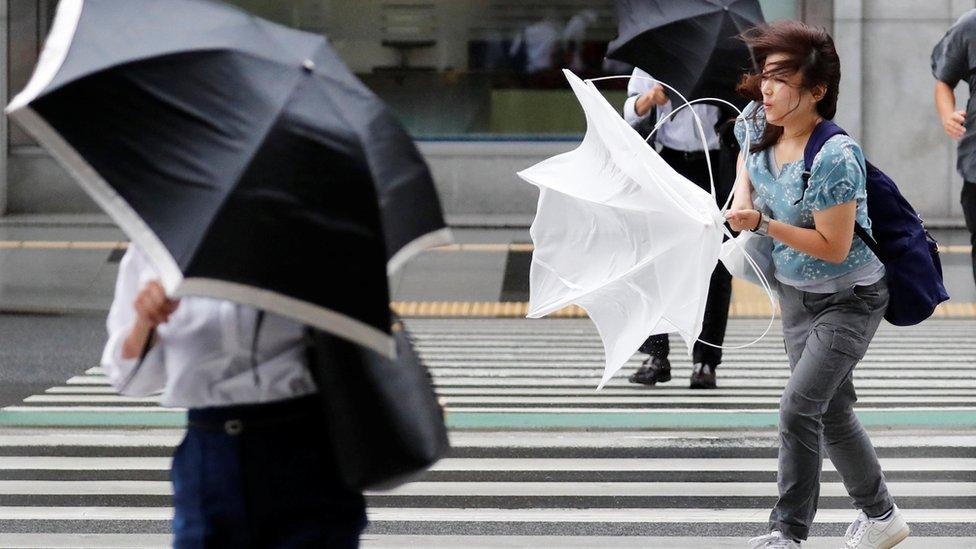 Жінка з парасолькою, яку вивернув вітер, на пішохідному переході