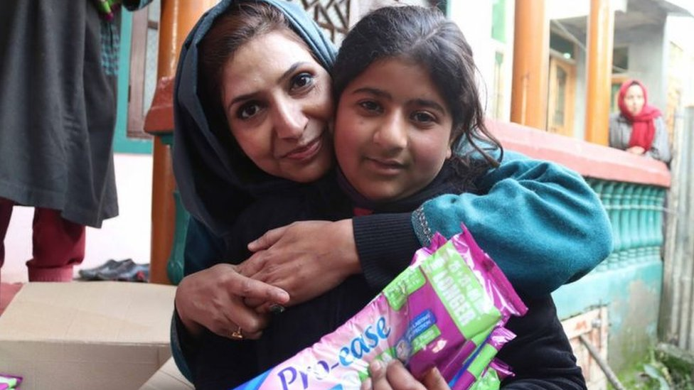Irfana Zargar hugging a teenager who just got sanitary pads from her