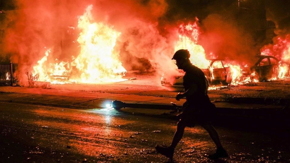 美國威斯康辛州基諾沙市一名男子走過被示威者縱火焚燒的汽車(25/8/2020)