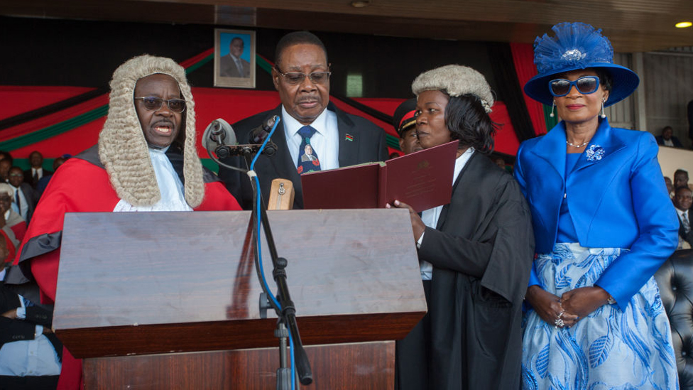 Malawi's President elect Arthur Peter Mutharika is sworn in for his second term by Chief Justice Andrew Nyirenda (L) and Registrar of the high Court and Supreme Court Of appeal (2R) as First Lady Gertrude Mutharika looks on