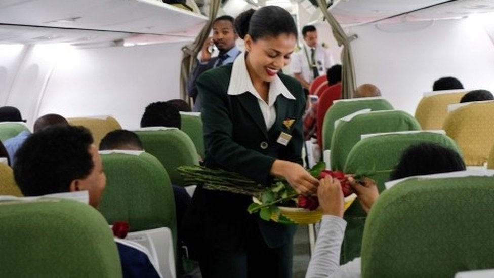 """Passengers are welcomed by cabin crew inside an Ethiopian Airlines flight who departed from the Bole International Airport in Addis Ababa, Ethiopia, to Eritrea""""s capital Asmara on July 18, 2018"""