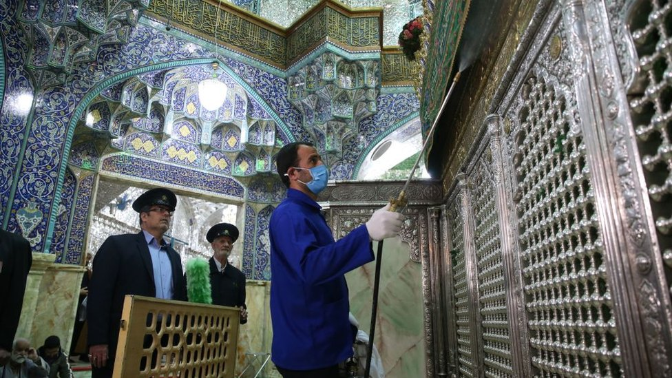 Petugas kebersihan Iran menyemprotkan disinfektan pada kuil Masumeh di kota Qom.