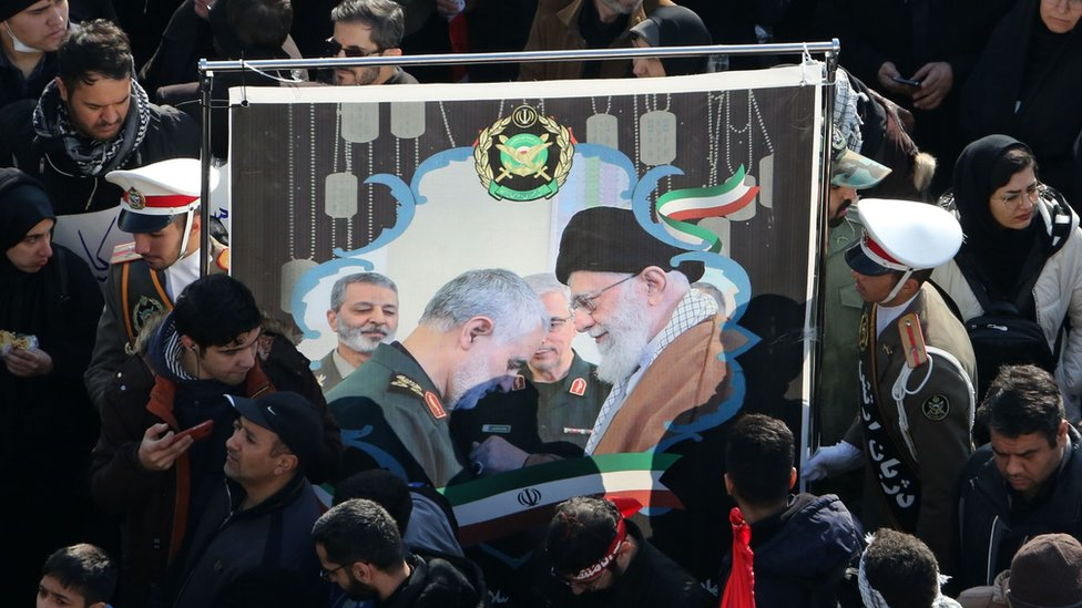 Mourners hold up a picture of Iran's supreme leader and Qasem Soleimani
