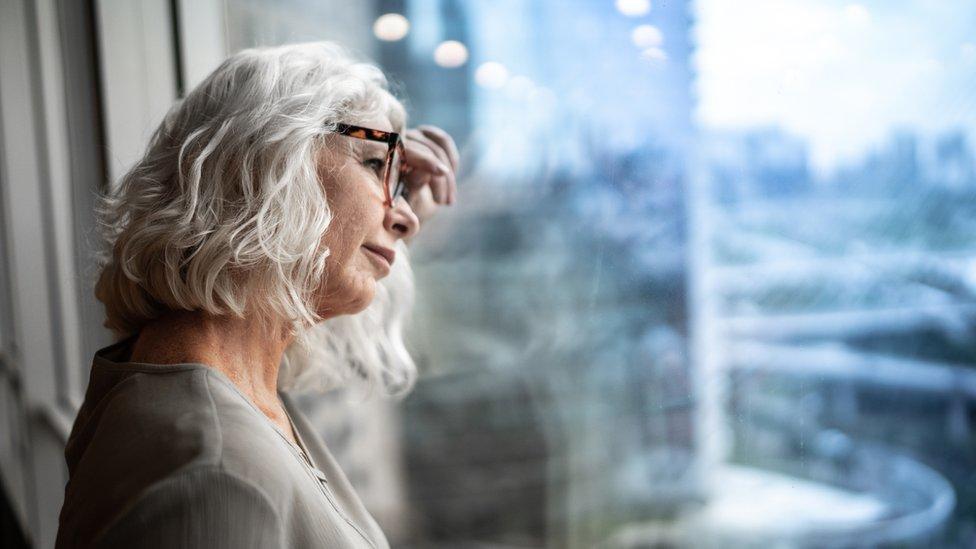 Una mujer mira por la ventana.
