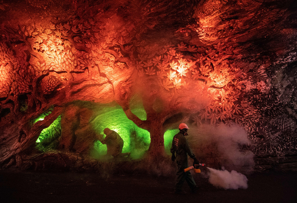 Workers disinfect a salt cavern covered in carvings and lit in red and green