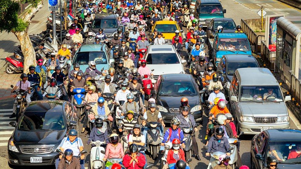 Una calle colapsada de motociclistas y autos.