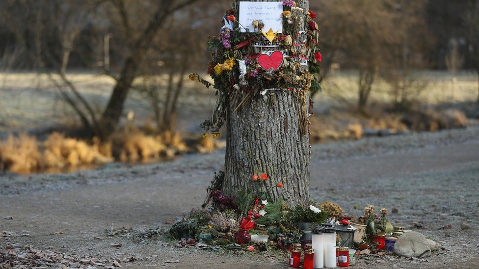 Flowers, candles and messages left by mourners adorn a tree near the spot where the medical student was raped and murdered