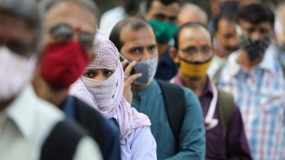 People wearing protective masks wait in line to board a bus amidst the spread of the coronavirus disease (COVID-19) in Mumbai, India, October, 6, 2020
