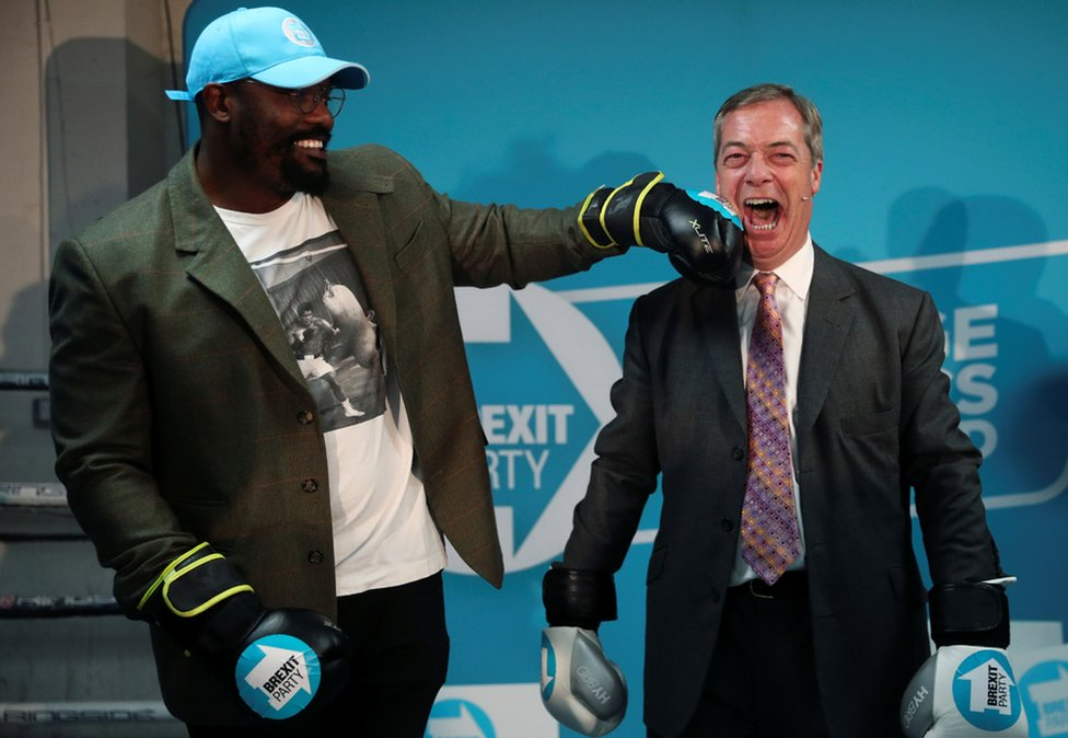 Brexit Party leader Nigel Farage poses with boxer Dereck Chisora during a visit to a boxing gym in Ilford, Essex.