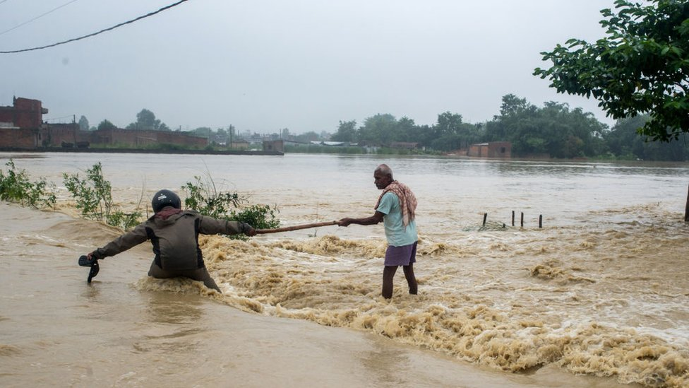Nepali residents use a stick to help each other cross a flooded area in the Birgunj Parsa district of the country.