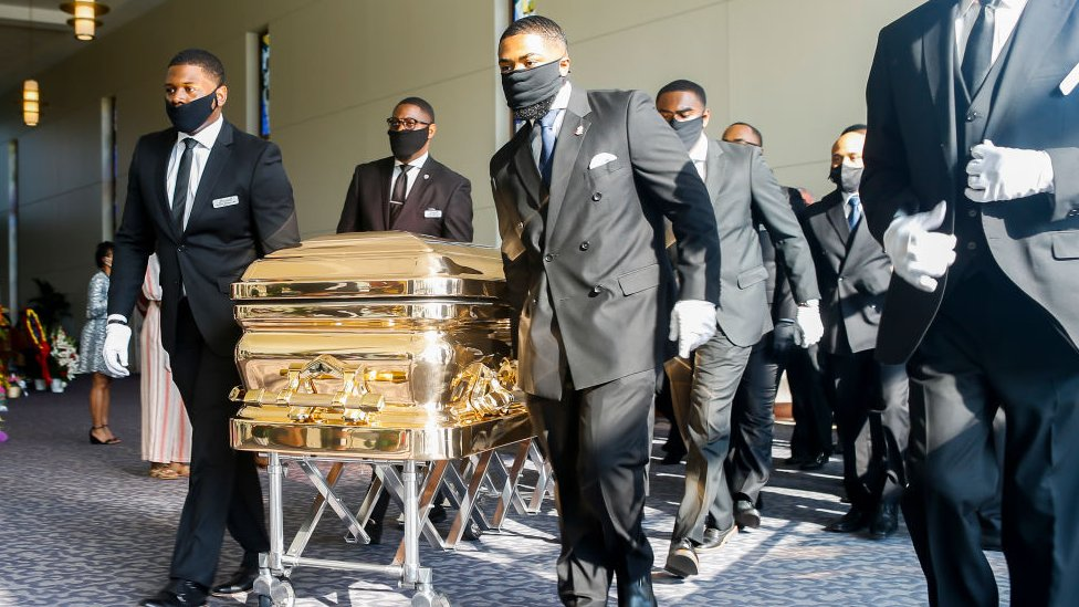 Pallbearers bring the coffin into the church