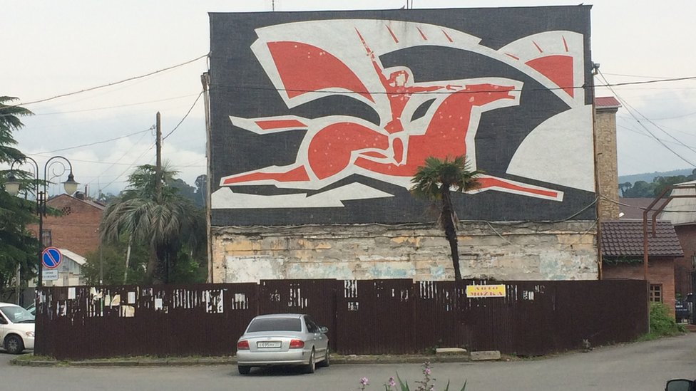 street art of a warrior atop a horse, soaring through the air, with sword upright