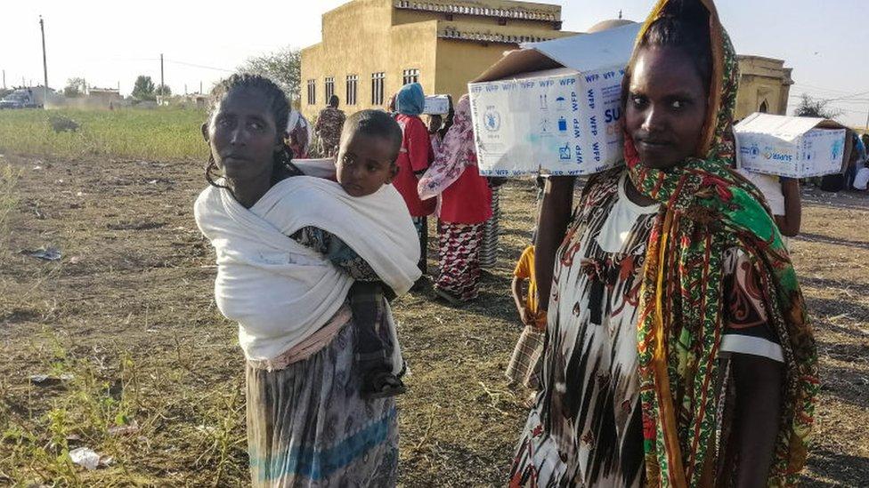 امرأتان ، إحداهما تحمل طفلاً والأخرى تحمل صندوقًا على كتفها