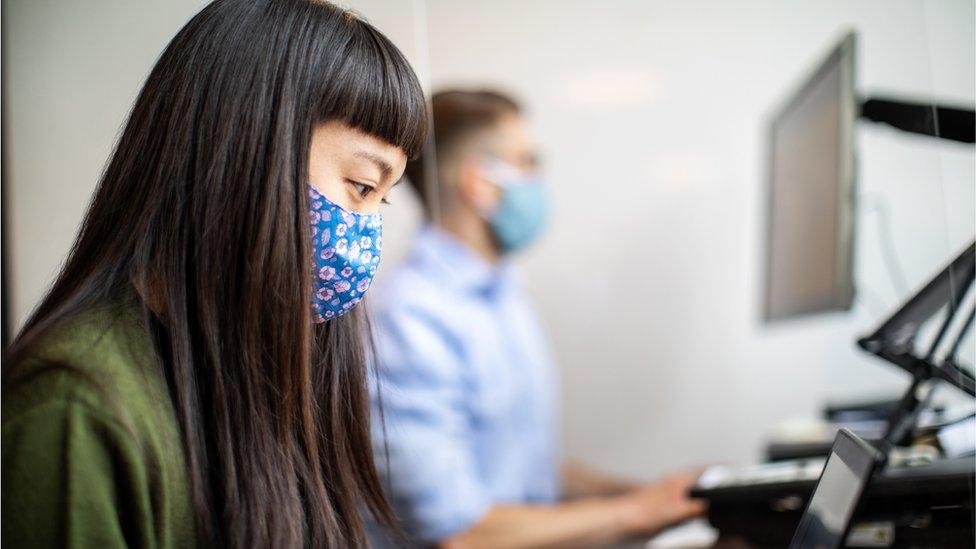 Una empleada usando mascarilla en una oficina