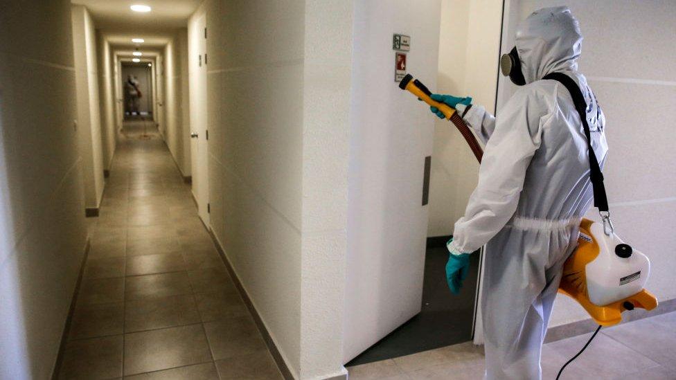 Personal desinfectando edificio en Chile.
