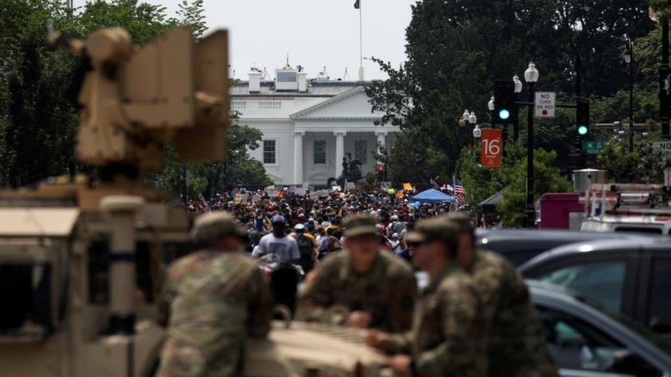 Manifestantes cerca de la Casa Blanca, en Washington D.C., siendo vigilados por soldados.