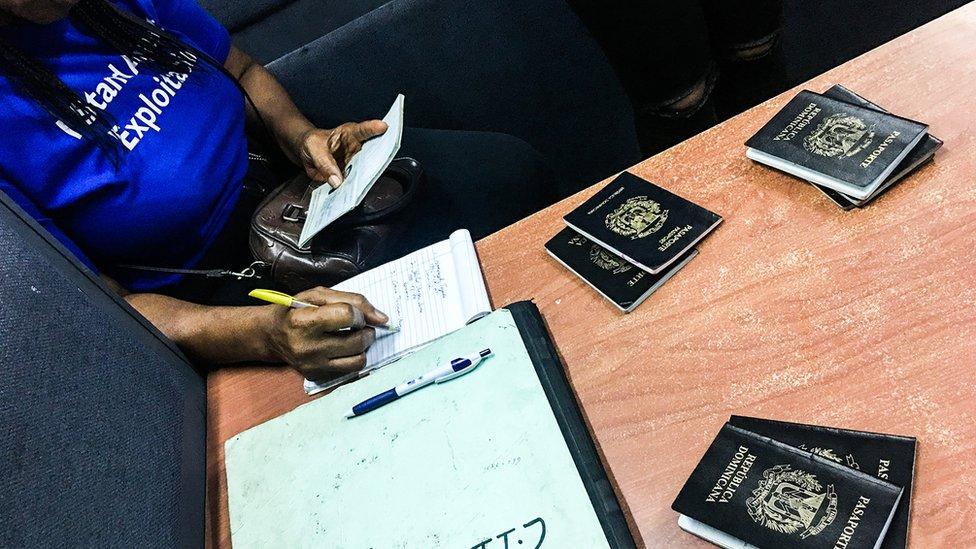 Una agente registra los pasaportes incautados en las redadas contra los traficantes humanos.