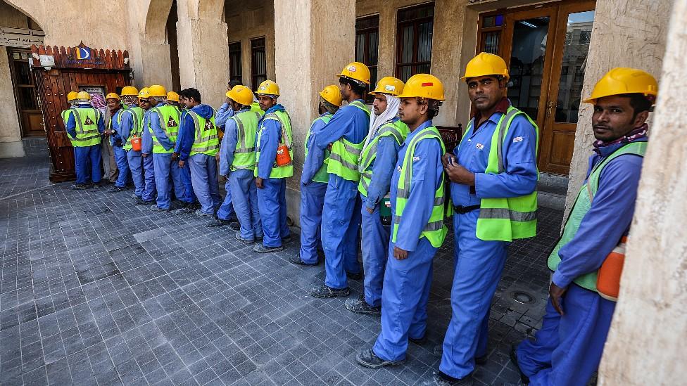 Trabajadores migrantes en Doha, Qatar, haciendo fila para usar un cajero automático