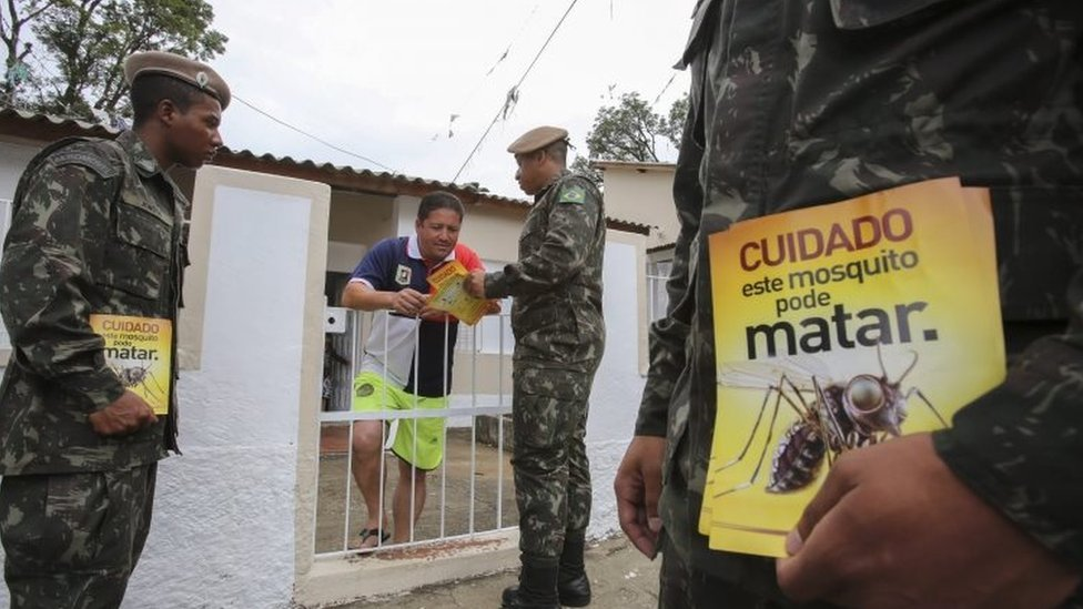 """Brazilian soldiers give a resident in Sao Paulo leaflets that read: """"This mosquito can be deadly"""". Photo: 29 January 2016"""