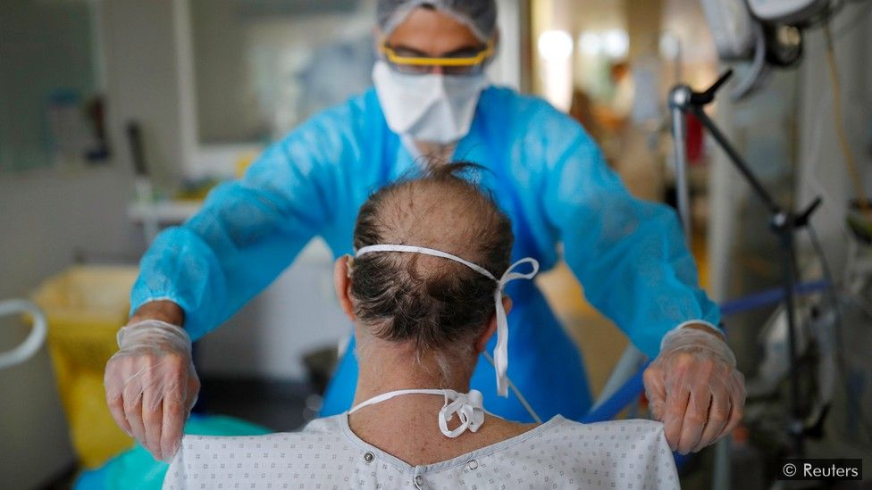 Doctor examines a patient sitting with his back to the camera
