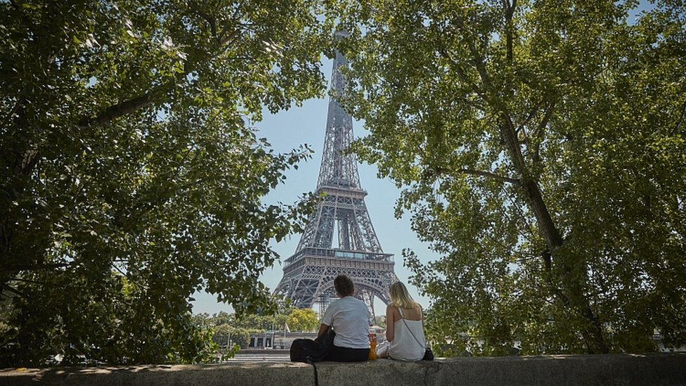 Tourists relax in the shade overlooking the Eiffel Tower. 25 June
