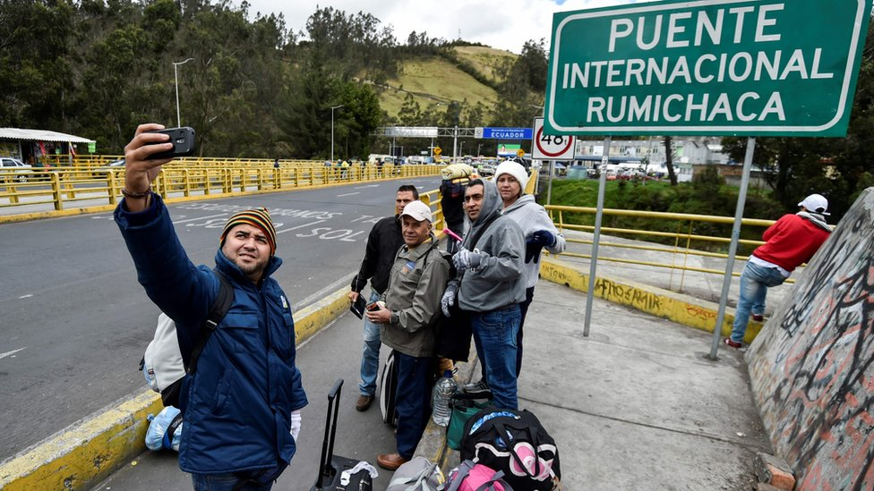Venezuelans pose for a picture at the Rumichaca international bridge before crossing from Ipiales in Colombia, to Tulcan in Ecuador, on August 20, 2018