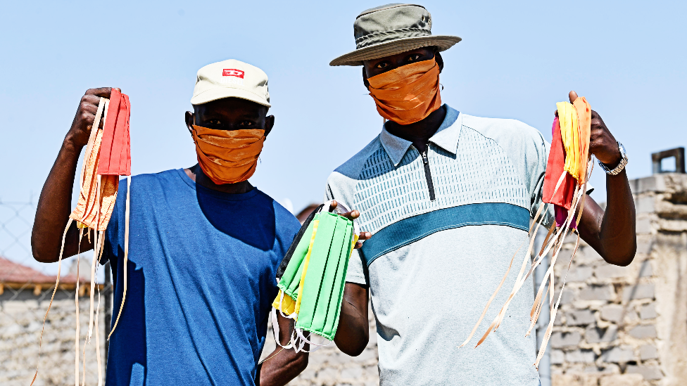 Men wearing and holding up face masks in South Africa's Nkowankowa Township during lockdown - 27 April 2020