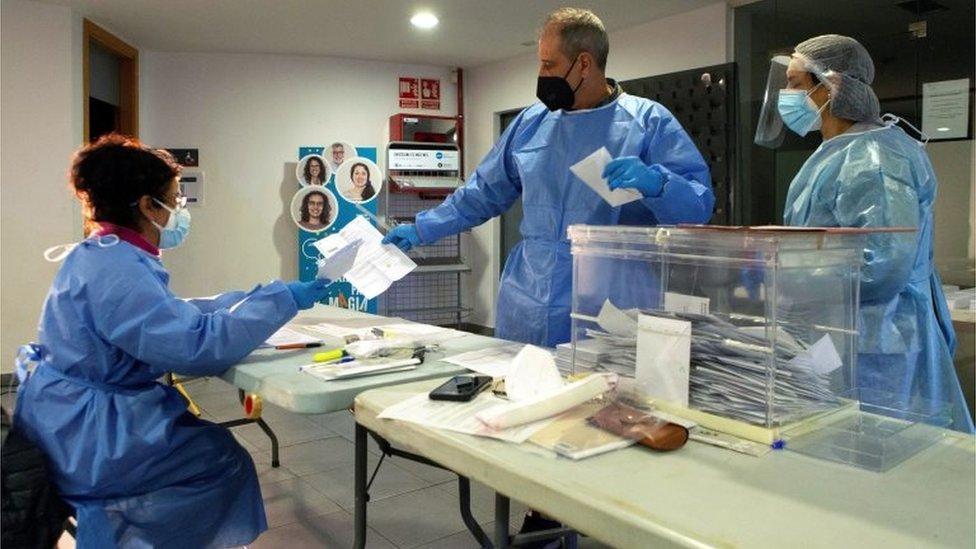 Funcionarios de casilla con trajes protectores en Barcelona