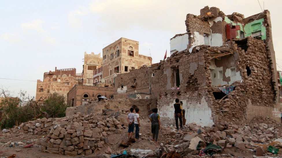 Yemeni children look at buildings that were damaged by air strikes carried out by the Saudi-led coalition on March 23, 2016