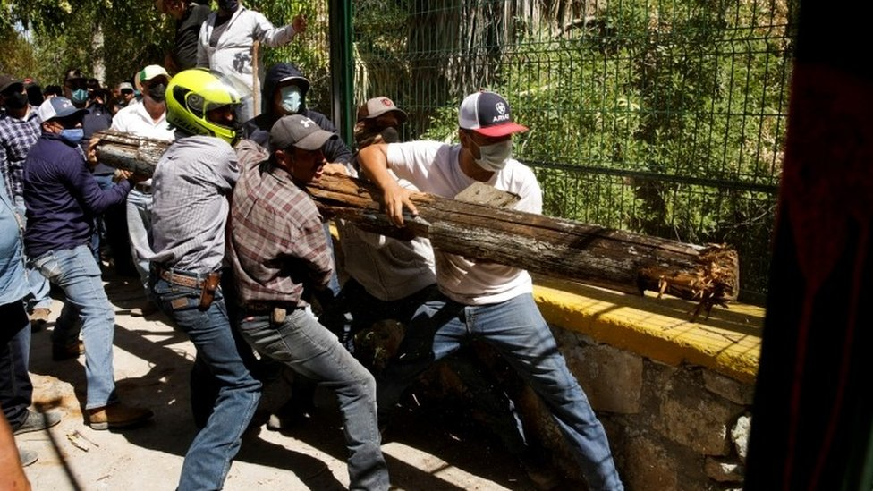Farmers hold a wooden trunk as they try to open a door to enter La Boquilla dam during a protest