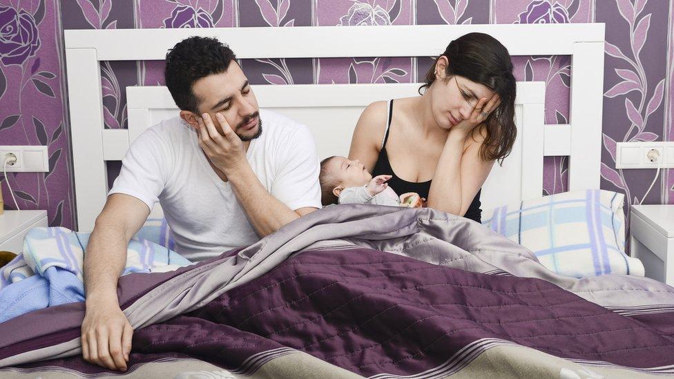 Padres en una cama con el bebé en medio.
