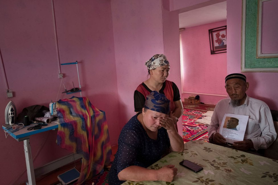 Gulnar Kosdaulet, 46, Gulzira Auelkhan, 40, Akbar Yenkelesh, 77, in their home in the village of Akshi near (100miles+) the border with China. Kosdaulets husband is still being held in a camp in Xinjiang. Auelkhan was detained in the camps in Xinjiang for 18 months. Yenkelesh, the father of Kosdaulets husband, holds up a photo of his son, Sarsenbek Akbar, 45.
