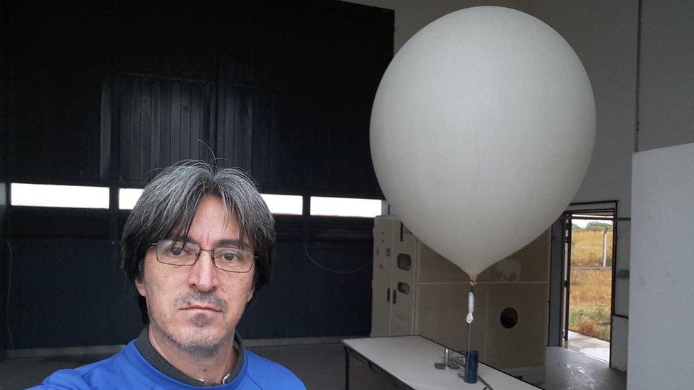 Víctor Oviedo con un globo sonda detrás.