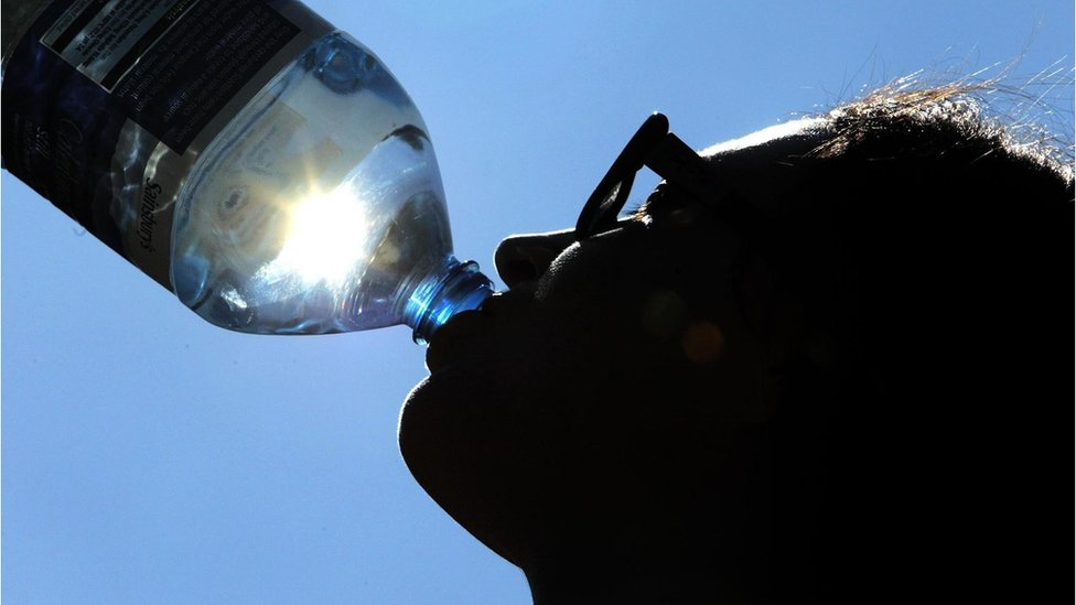Drinking water from a bottle