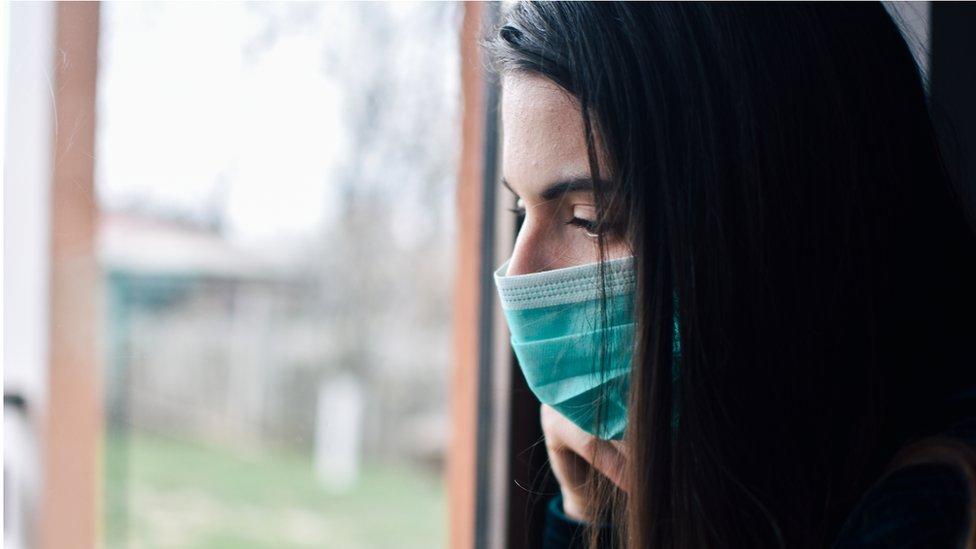 Woman looks through a window