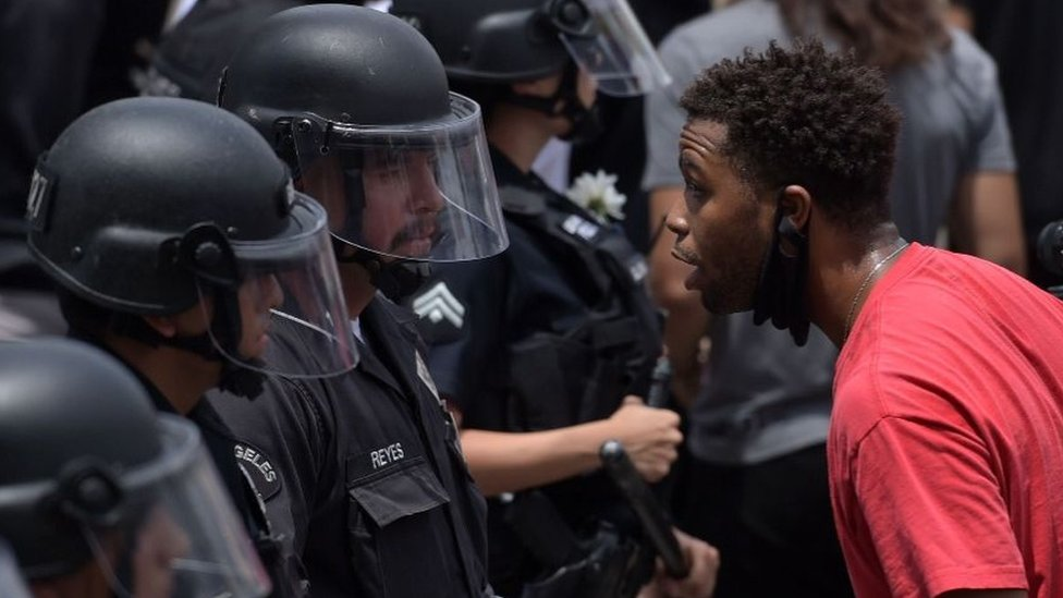 A protester speaks with an LAPD officer during a demonstration over the death of George Floyd in Hollywood, California on June 2, 2020. (AFP)